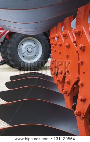 Detail of orange plough for a Farming Tractor and wheel