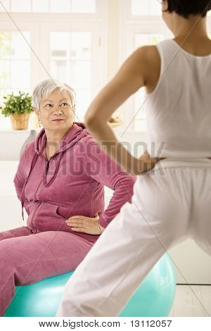 Elderly woman sitting on fit ball looking at personal trainer demonstrating exercise.?