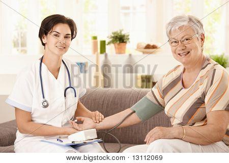 Enfermera de la presión arterial medición de mujer senior en casa. ¿Mirando a cámara, sonriendo.?