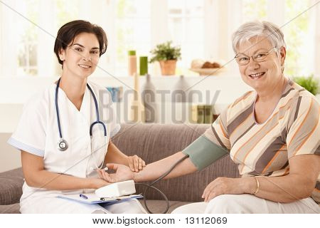 Nurse measuring blood pressure of senior woman at home. Looking at camera, smiling.?