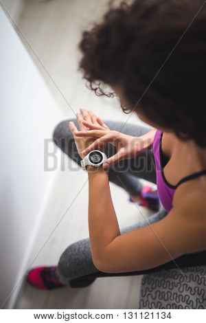 Woman checking her workout time on a watch.