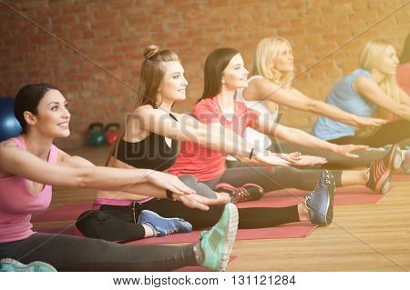 Cheerful sporty girls are doing exercise in group. They are sitting and smiling. The ladies are stretching arms to leg