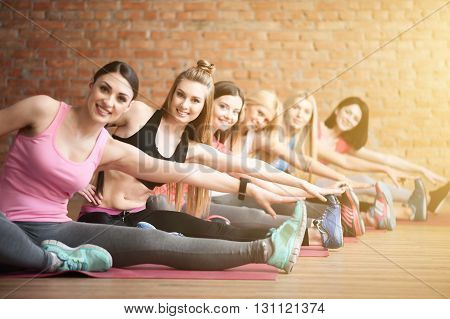 Beautiful young women are going for sports. They are sitting and exercising with joy. The ladies are looking at camera and smiling