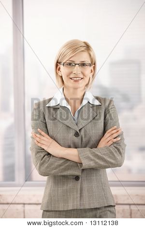 Confident businesswoman in office, smiling with arms folded.?