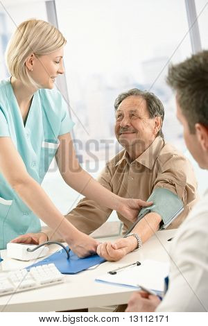 Smiling nurse measuring blood pressure of elderly patient, smiling at doctor's desk.?