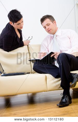 Young businesspeople working together, sitting at couch in office. Man writing notes in personal organizer.