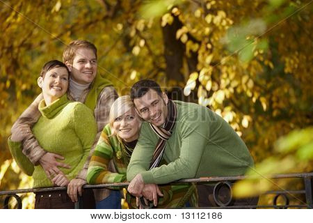 Portrait of happy young friends standing in autumn park, leaning to railing, smiling.?