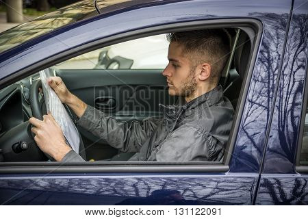 Side view of young handsome man sitting in car and reading document