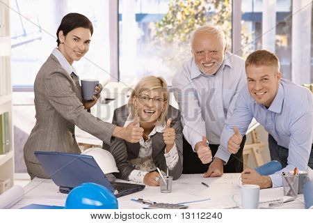 Portrait of happy businessteam giving thumbs up at work, smiling at camera.