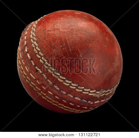 Old worn Cricket Ball on black background