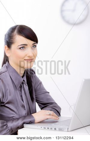 Profile portrait of young businesswoman using laptop computer at office desk, looking up, smiling.