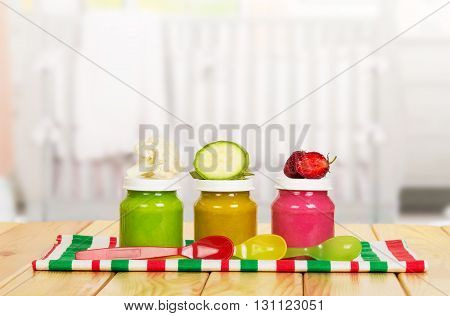 Three jar with puree for baby food on the background of the kitchen.
