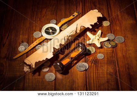 Old map, a compass, an hourglass and coins on the background of dark wood.