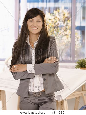 Pretty businesswoman with long hair standing in office with arms crossed, looking at camera, smiling.?