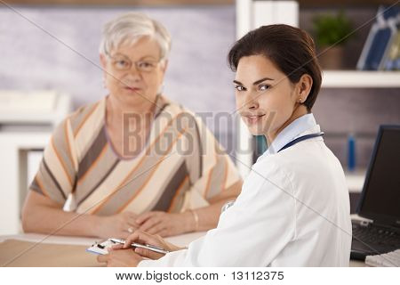 Portrait of female doctor talking to senior patient in office, looking at camera, smiling. Selective focus on doctor.?
