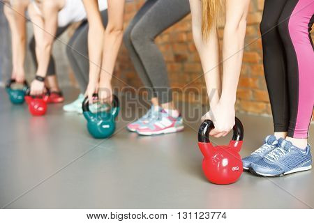 Close up of female legs and arms taking kettlebell from the floor. Young girls are standing in gym