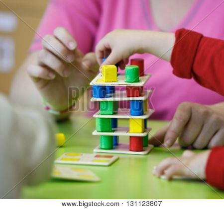 Children playing with homemade do-it-yourself educational toys stacking and arranging colorful pieces. Learning through experience concept gross and fine motor skills back to school concept.