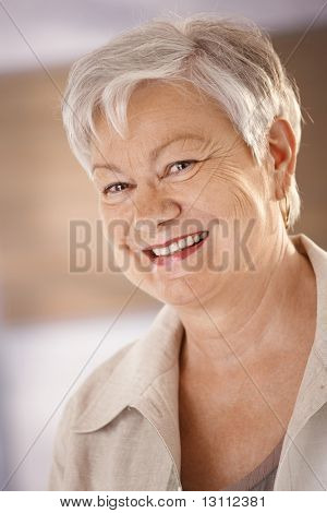 Closeup portrait of happy senior woman with white hair, looking at camera, smiling.?