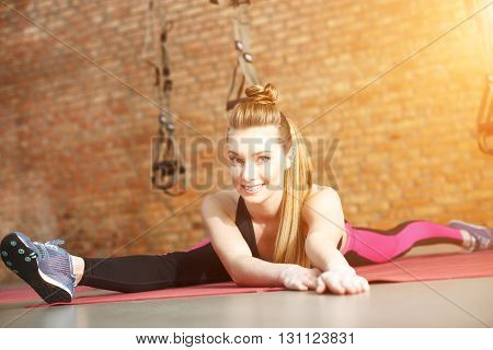 Beautiful young girl is doing splits and smiling. She is stretching arms forward