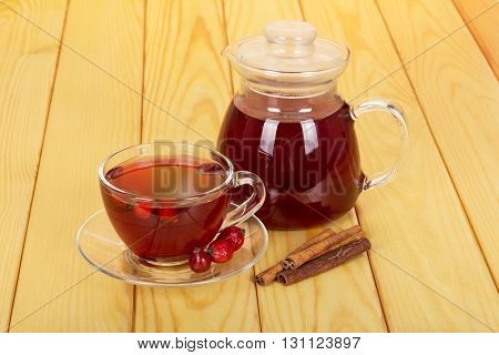 Jug with a drink and a cup of tea rosehip berries on a background of light wood.