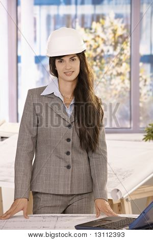 Businesswoman with long dark hair standing in office wearing hardhat, smiling at camera.?