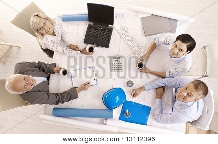 Team meeting in office, businesspeople smiling, looking up at camera, high angle view .?