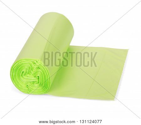 A roll of green plastic garbage bags isolated on a white background.
