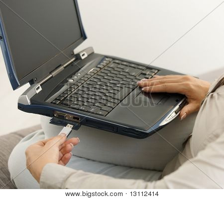 Closeup of plugging in flash drive into laptop computer. Copyspace on blank screen.?