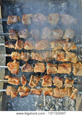 A close up of the cooking shashlik on skewers.