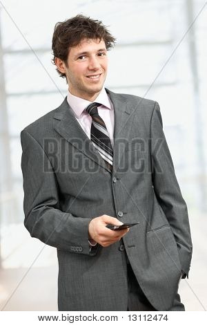 Young businessman standing with hand in pocket, using mobile phone, smiling. ?