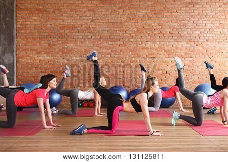 Cute group of women are doing fitness exercise. They are kneeling and raising leg up. The girls are smiling