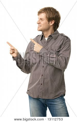 Casual young man pointing to blank space, smiling. Copyspace, isolated on white, side view.?