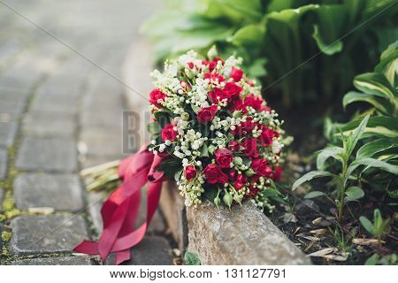 Bouquet of beautiful flowers and greenery is on the green grass.