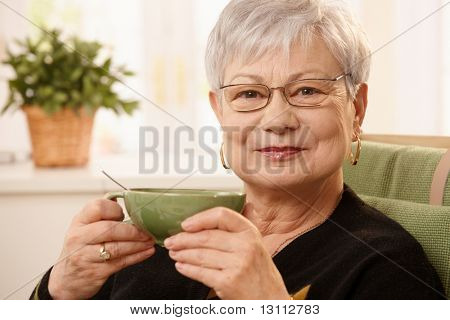 Closeup portrait of mature lady sitting at home holding teacup, looking at camera.?