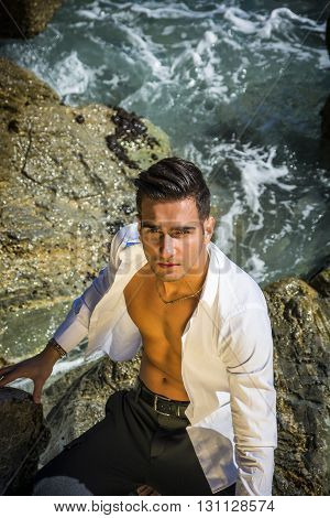 Young handsome man with open shirt on naked torso, on beach looking at camera. Seen from above. Sea waves on background