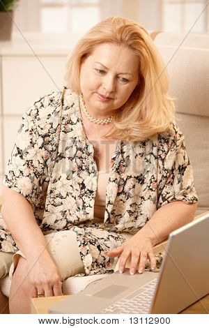 Senior woman working with laptop computer with small smile, typing