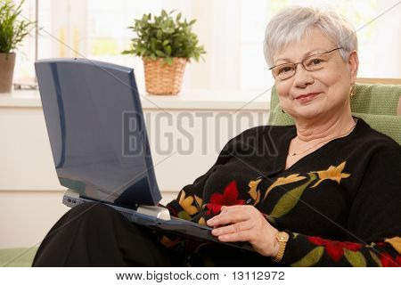 Smiling elderly lady holding laptop computer, sitting in armchair, smiling at camera.?