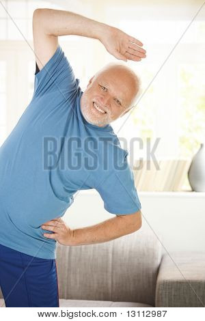 Cheerful senior doing sport exercises in living room, smiling at camera.?