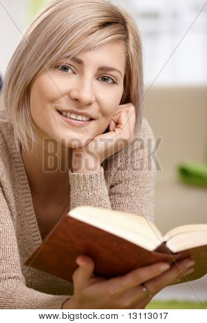 Young blonde woman lying on floor at home reading book, looking at camera, smiling.?
