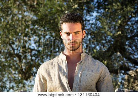 Ruggedly Handsome Man Among Trees with Shirt Unbuttoned Relaxing in Warm Sunlight