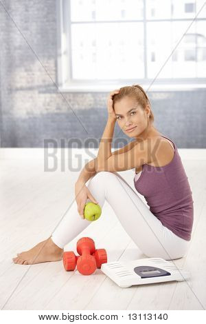 Portrait of pretty sporty girl sitting on floor in gym, holding green apple, with scale and dumbbells, smiling at camera.?
