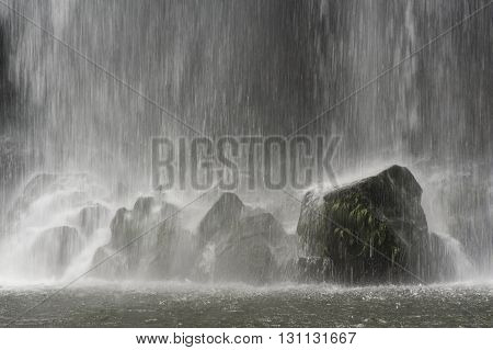 Water falling onto rocks with a dark background
