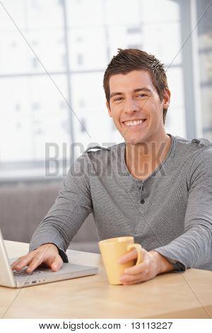Happy young man sitting at table at home, smiling at camera, having tea, using laptop computer.?