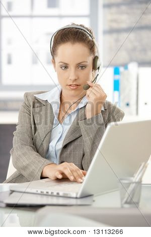 Young attractive dispatcher working in bright office, using headphones and laptop.?
