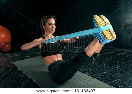 The brunette athletic woman exercising with rubber tape on black wooden floor