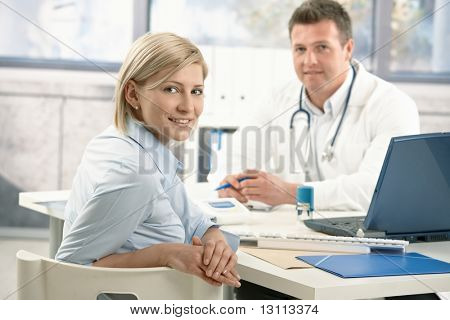 Smiling woman sitting in doctor's office on appointment, looking at camera, doctor in background.?