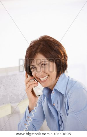 Portrait of senior office worker talking on landline phone, laughing.?