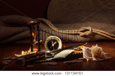 Old compass, an hourglass, knife, money, and seashells on a background of dark wood.