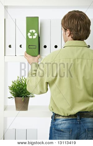 Young environmentalist man pulling out green folder from office shelf.?