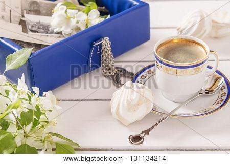 Casket with old photos, cup of coffee, marshmallows and branches of apple blossom on a white wooden background